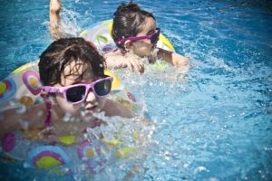 two kids with sunglasses playing in the pool with floaties