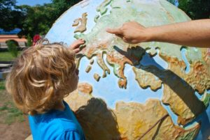 ASD kid looking at a globe - ABA blog