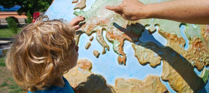 kid looking at a globe